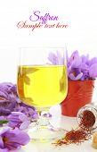 Glass off saffron tea and saffron flowers
