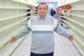 Elderly Man Stands Between Empty Shelves In  Shop With Dissolved