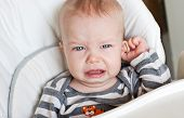 foto of inflamed  - cute little boy crying and holding his ear on a white background - JPG