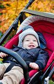 Happy Baby Boy Sitting In A Stroller