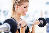 stock photo of dumbbells  - Woman in gym lifting weights - JPG