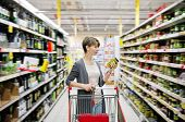 stock photo of grocery cart  - pretty woman with a cart shopping and choosing goods at the supermarket - JPG