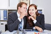Business man telling woman a secret by whispering it into her hear