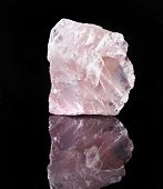 Natural Rose Quartz crystal with reflection on black surface background