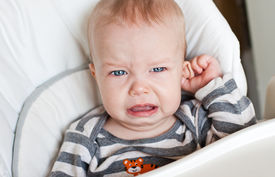 stock photo of groping  - cute little boy crying and holding his ear on a white background - JPG