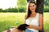 Beautiful Girl Reading A Book In The Garden In Summer
