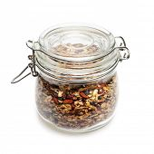 Homemade granola stored in glass jar isolated on white background