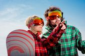 Woman Point The Finger To Man On Somewhere Dressed In Ski Suits On Blue Sky Background