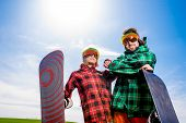 Cool Couple With Snowboards In Sport Wear Standing On The Grass In The Green Field With Blue Sky