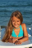 Little girl in bright sunshine at the seaside - laying on beach chair