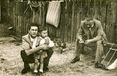 LODZ, POLAND, CIRCA 1950's: Vintage photo of father and grandfather with a little girl on farm