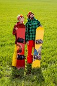 Couple In Sport Wear With Snowboards Standing On The Grass And Watching Up