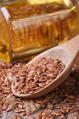 image of flax seed oil  - Flax seed in a wooden spoon on a background of the bottle with oil - JPG