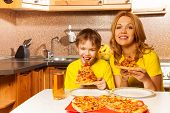 Portrait of boy and mother ready to eat pizza