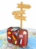 wood sign board and old suitcase with striples flags on blurred world map