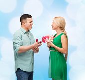 happiness, holidays, celebration and couple concept - smiling couple with flower bouquet and ring in