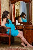 Pregnant Woman Sits Before Dressing Table.