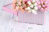 Flowers in gift box on wooden table close-up