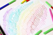 Kids drawing and colored pencils on wooden table