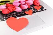 Red hearts and flowers on computer keyboard close up