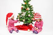 stock photo of identical twin girls  - Twin babies decorating a Christmas Tree and having fun - JPG