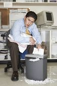 Overworked businessman shredding documents