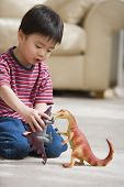 picture of dinosaur-eggs  - Young boy playing with toy dinosaurs - JPG
