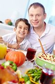 Joyful kid with his father sitting at festive table and looking at camera