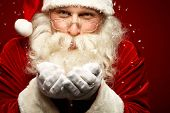 stock photo of blowing  - Playful Santa Claus blowing snow and looking at camera - JPG