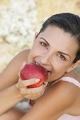 Young woman biting apple