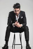 Elegant fashion man in tuxedo looking at the camera while sitting on a stool, holding his hands.