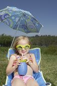 Young girl drinking juice in a lawn chair