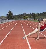 Male track athlete stretching