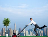 Green businessman in the city mowing lawn.