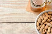 High angle shot of a glass of beer and a bowl of peanuts on a white wood table. Horizontal format with copy space.