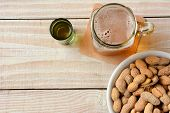 High angle shot of a glass of beer, a whiskey shot and a bowl of peanuts on a white wood table. Horizontal format with copy space.