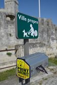 LA ROCHELLE, FRANCE - JUNE 24, 2013: Point with bags for dog droppings under the sign of municipal program