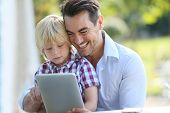Portrait of man with son using digital tablet