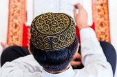 Asian Muslim man reading Koran or Quran on praying carpet wearing traditional dress