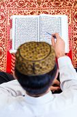 stock photo of quran  - Asian Muslim man reading Koran or Quran on praying carpet wearing traditional dress - JPG