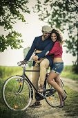 Happy couple having fun while biking on a country road