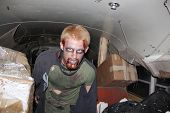 MUSKOGEE, OK - Sept. 13: Bloodied zombie comes from the dark to enter a school bus during the Castle Zombie Run at the Castle of Muskogee in Muskogee, OK on September 13, 2014.