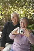 Senior Asian couple sitting on a park bench with a digital camera