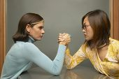 Businesswomen arm-wrestling