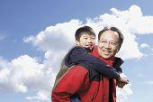 Asian father giving son piggyback ride outdoors