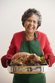 Senior Hispanic woman holding roasted turkey