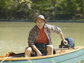 Hispanic man smiling in small boat