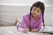 Young Hispanic girl doing homework on the floor