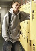 Young Asian man next to school lockers