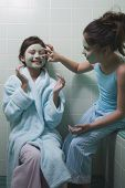 Two young girls applying facial masks in bathroom